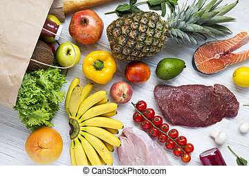Paper bag of various health food on white wooden table. Healthy food background, top view. Healthy eating.