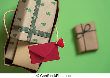 Paper bag with Christmas gifts and red envelope. Above view and close-up.