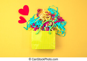 Paper bag with colored streamers on a bright yellow background Red heart concept of Valentine's day