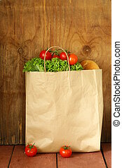 paper bag with food, lettuce, tomatoes, bread on a wooden...