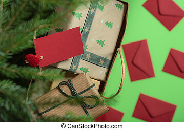 Paper bag with gifts under Christmas tree and paper note. Above view. Christmas gifting.