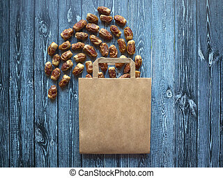 Paper bag with scattered dates on a dark wooden table