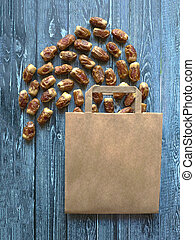 Paper bag with scattered dates on a wooden background