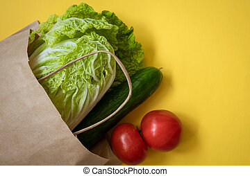 Paper bag with vegetables on a yellow background