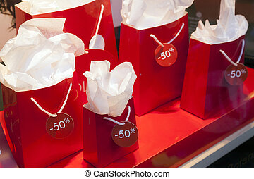 paper bags with sale signs in display window of shop