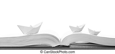 Paper boats on the opened book on a white background