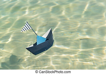 Paper boat floating on water - Blue paper boat floating on ...