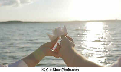 Paper boat in the hands of lovers floating on a sunny path
