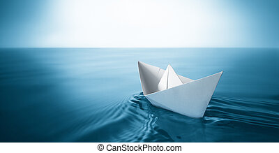paper boat - origami paper sailboat sailing on blue water