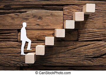 Paper Businessman Climbing Block Ladder On Wood
