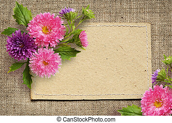 Paper card and aster flowers on beige canvas background