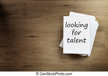 looking for talent - Paper card on a wooden table with text...