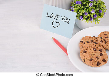"""Paper card with """"love you"""" text with red pen and cookies"""