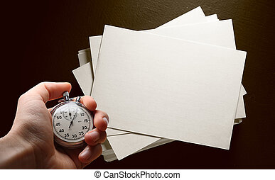 Paper cards on black and hand with stopwatch