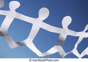 Chain of paper people against blue sky