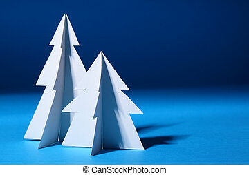 Paper Christmas trees over blue background