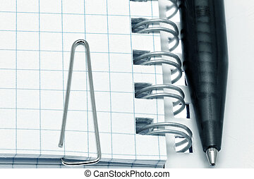 Paper clip  on notebook pages with pen. Isolated over white.