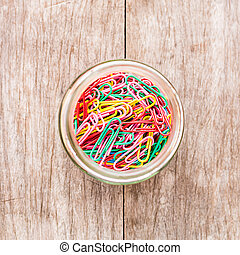 Paper clips in bottle on a wooden background