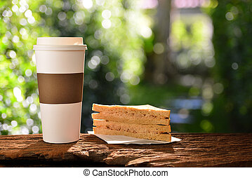 Paper cup of coffee and sandwich in the garden