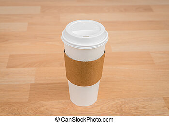 Paper cup of coffee on wood background