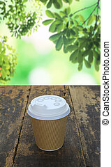 paper cup of coffee on wood table