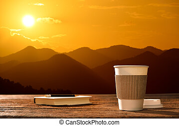 Paper cup of coffee with mountain background at sunrise