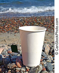 Paper cup on the pebbles