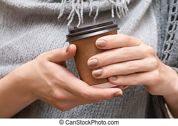 Paper cup with coffee in female hands