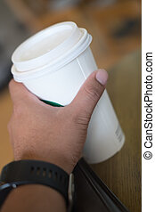 Paper cup with coffee in hand