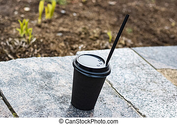 Paper cup with coffee on a concrete bench