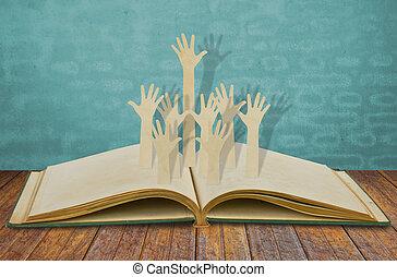 Paper cut of Hands volunteering or voting on old book