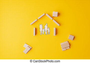Paper cut silhouette of a family in house made of wooden blocks