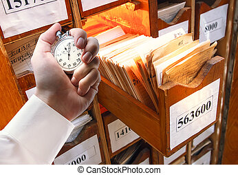 Paper documents in archive and stopwatch in male hand -...
