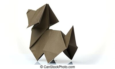 Paper dog figurine on white background. Origami dog made by child. Simple design of paper animal.