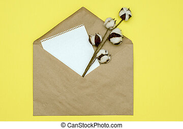 paper envelope with a page of paper and a branch of cotton from it on a yellow background. mockup with copy space
