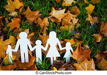 Paper family on autumn grass