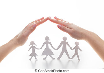 Paper family under hands in gesture of protection.