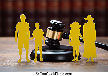 Paper Family With Mallet On Table In Courtroom - Closeup of...