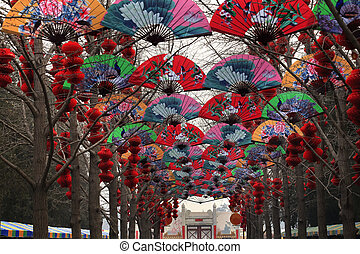 Paper Fans Lucky Red Lanterns Chinese New Year Decorations Stone Gate Ditan Park Beijing China. During Lunar New Year, many parks and temples in China have large outdoor fairs, festivals. Chinese characters on lanterns say lucky and long life.