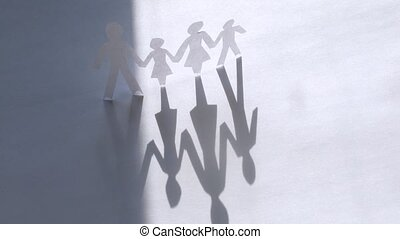 Paper figures of family strong hold hands on white, time lapse