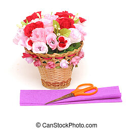 Paper flower in a basket with colorful paper and scissors
