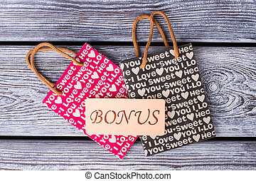 Paper gift bags on wooden background.