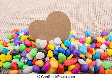 Paper heart amid pebbles on canvas ground