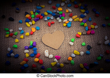 Paper heart amid pebbles on canvas ground - Paper heart amid...