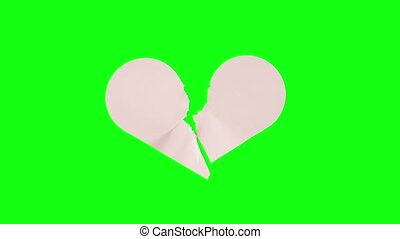Heart-shaped sheet of paper breaks in stop motion into two parts on a green background for the chroma key.