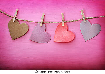 Paper hearts hanging from string with clothespins