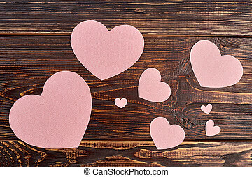 Paper hearts on brown wooden background.