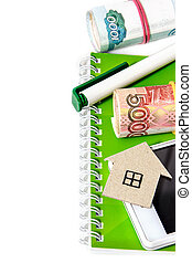 Paper house, Russian money, a pen and a notebook. Vertical edge