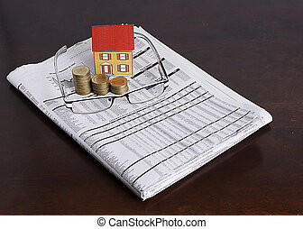 Paper house with coins stack and eyeglasses on news paper