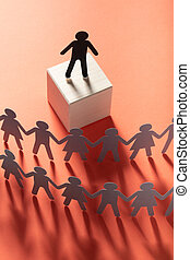 Paper leader figure in front of paper people holding hands on red surface. Leader, politician, boss.